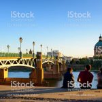 Toulouse, France - October 06, 2017: People are resting on the edge of the Garonne river against the Saint Pierre bridge and the dome of the Grave at the evening in Toulouse city of France.